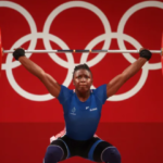Dora Tchakounte at the foot of a podium flown over by KUO Hsing-Chun